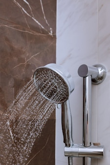 Fresh shower with water drops splashing. water running from shower head and faucet in modern bathroom.