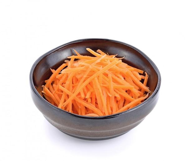 Fresh shredded carrots in bowl on white