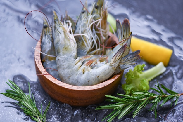 Fresh shrimp on bowl with rosemary ingredients herb and spices for cooking seafood - raw shrimps prawns on ice frozen at the seafood restaurant