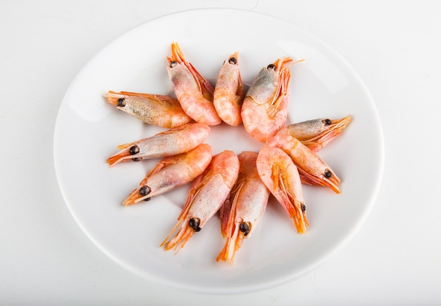 白い皿で揚げるための新鮮なエビ