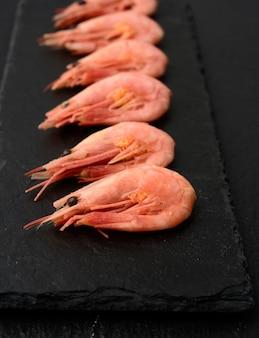 Свежие креветки подряд на черной грифельной доске, крупным планом