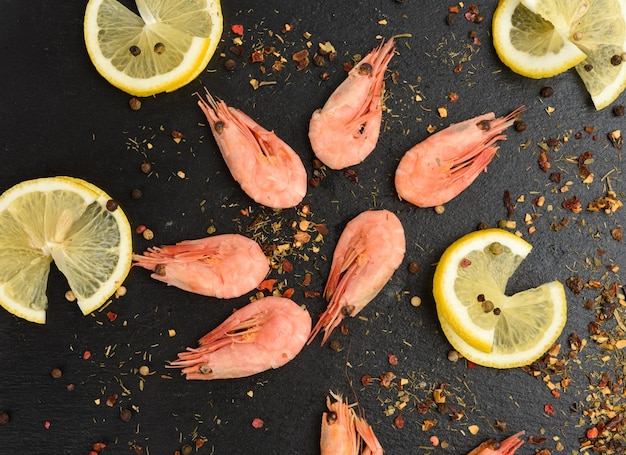 Fresh shrimp and lemon slices on black board, top view