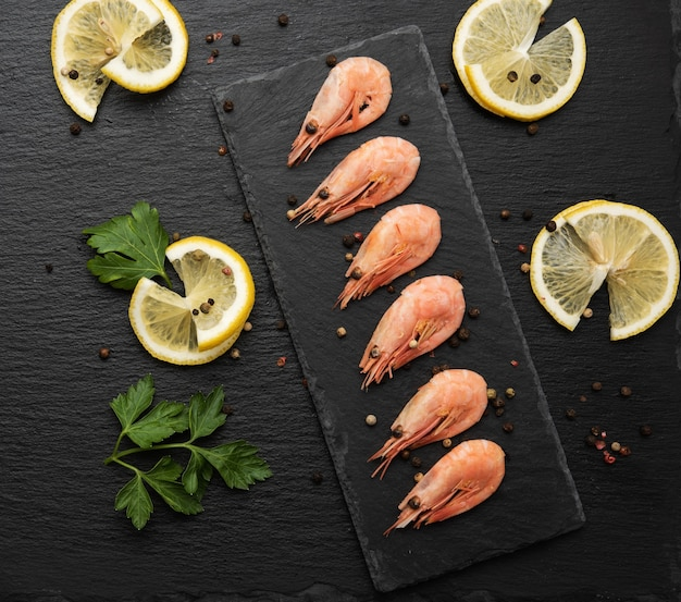Fresh shrimp in a row on a black slate board, top view