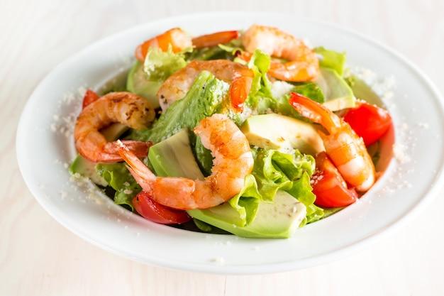 Fresh shrimp salad made of tomato, ruccola, avocado, prawns.