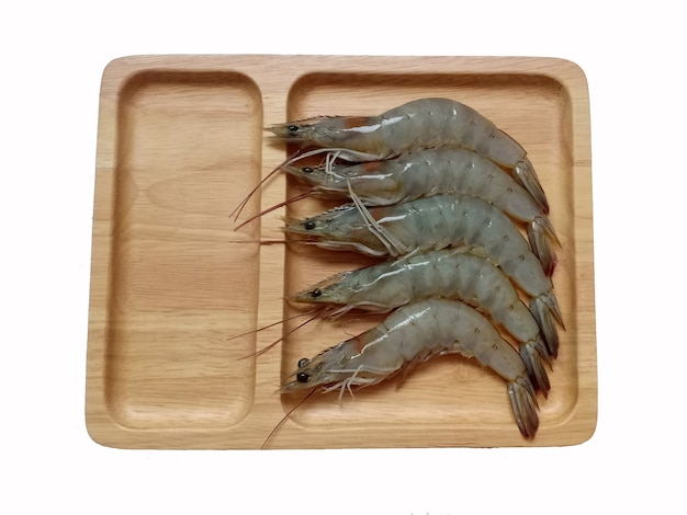 Fresh shrimp on the wooden plate isolated on the white background