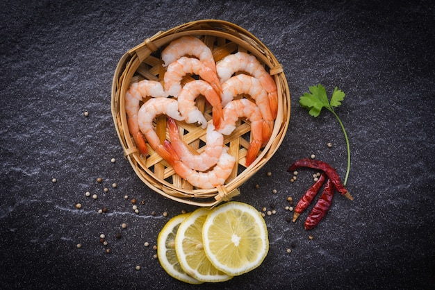 Fresh shrimps on bamboo steamers with spices lemon chilli on the dark plate