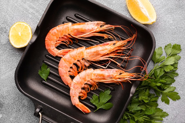 Fresh shrimps on pan with condiments