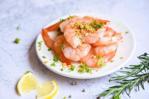 Fresh shrimps served on white plate with herbs and spice