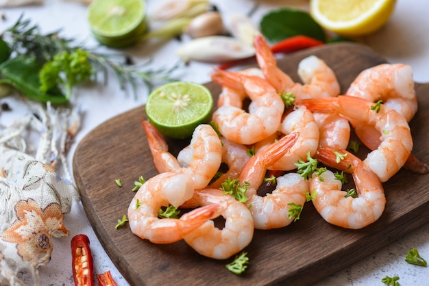 Fresh shrimps served on wooden cutting board