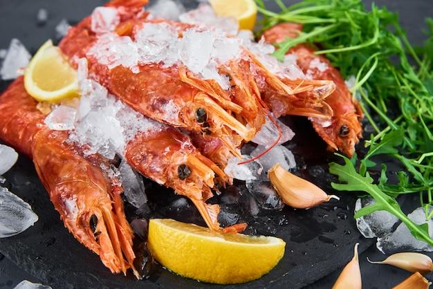 Fresh shrimps with lemon on dark background red raw prawns