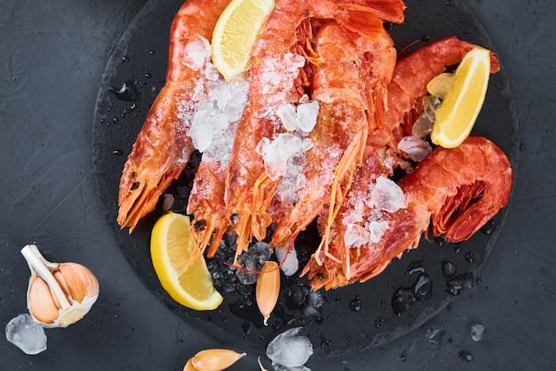 Fresh shrimps with lemon on dark background