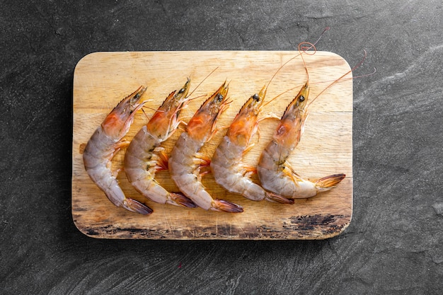 Fresh shrimps with wooden board on black stone