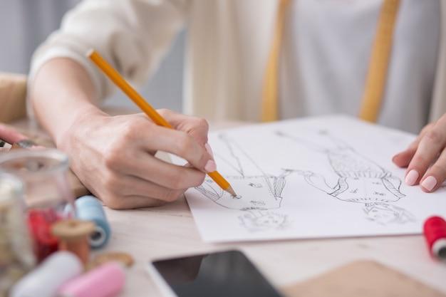 新鮮なスケッチ。スケッチを描いている間鉛筆を保持している魅力的な女性の手のクローズアップ