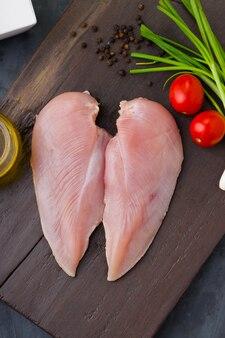 Свежее сырое куриное филе без кожи на деревянной доске
