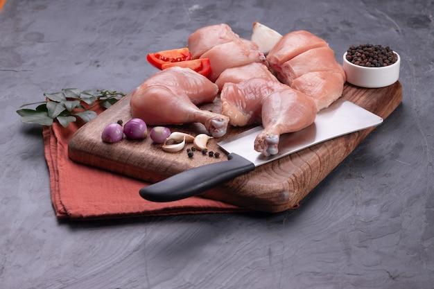 Свежие сырые куриные ножки без кожи, голени и сырая куриная грудка на коричневой деревянной основе