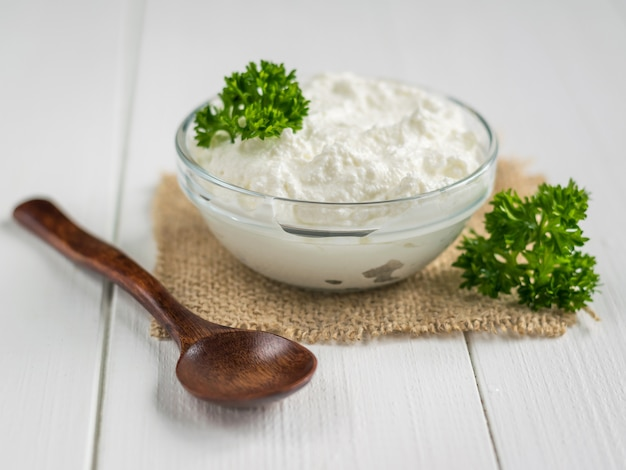 A fresh slice of bread smeared with cottage cheese cream with parsley on the table.
