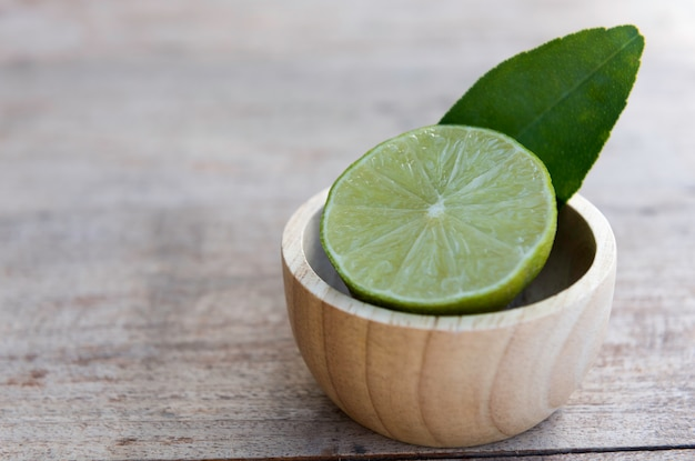 Fresh slice half  lime decoration in small wood bowl
