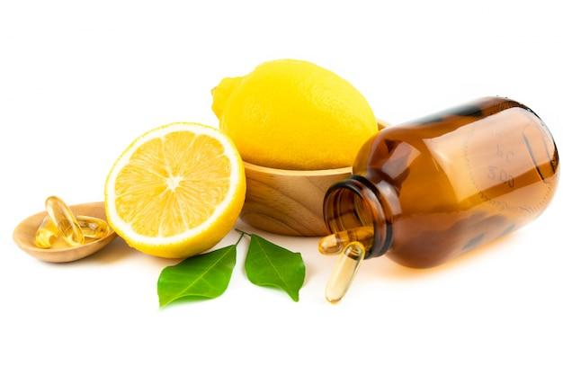 Fresh slice lemon and vitamin c capsule isolated on white background