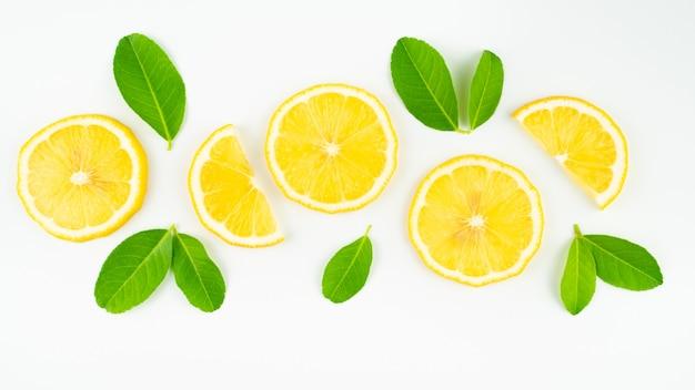 Fresh slice lemon with leaves isolated on white