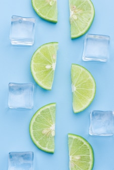Fresh slice lime with ice cube on blue