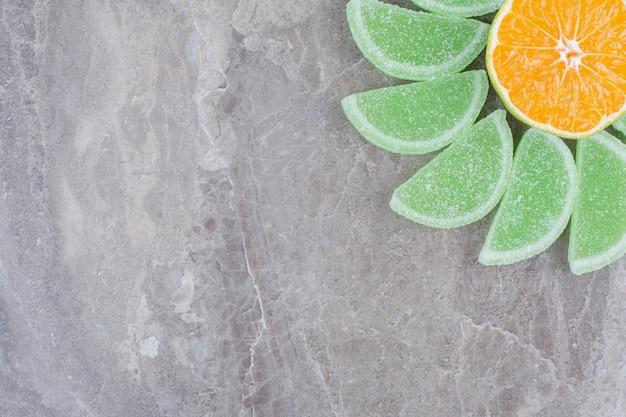 Свежий ломтик апельсина со сладким мармеладом на мраморном фоне.