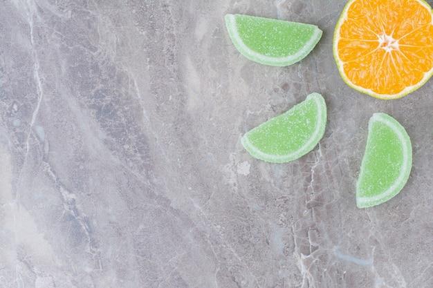 Fresh slice of orange with sweet marmalades on marble background.