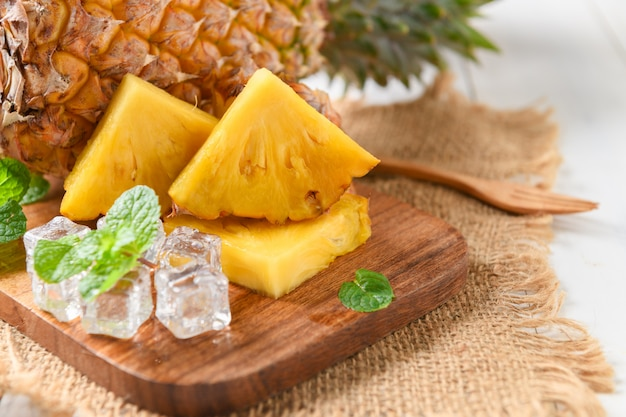 Fresh slice pineapple and ice on wood