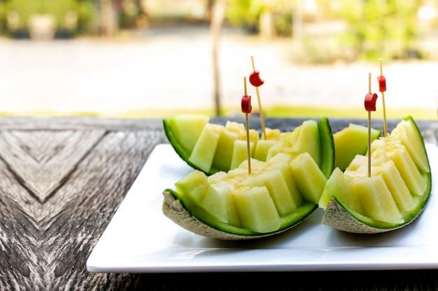 Fresh slice sweet green melon on white crokery put on wooden table.
