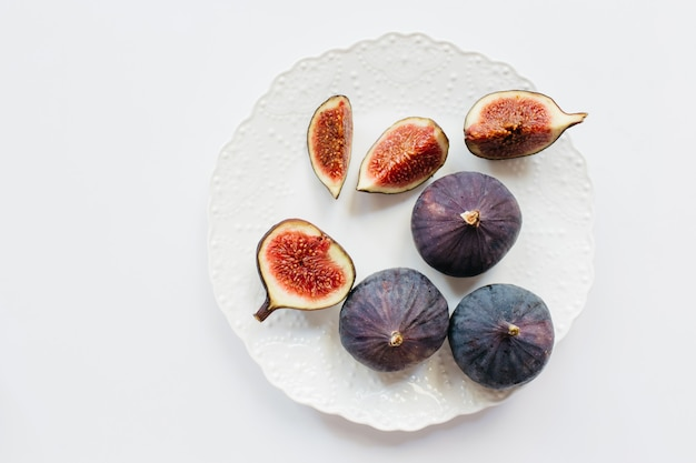 Свежие нарезанные и целые спелые инжир в тарелке на белом фоне. еда фото фон. плоская планировка, вид сверху. скопируйте пространство.