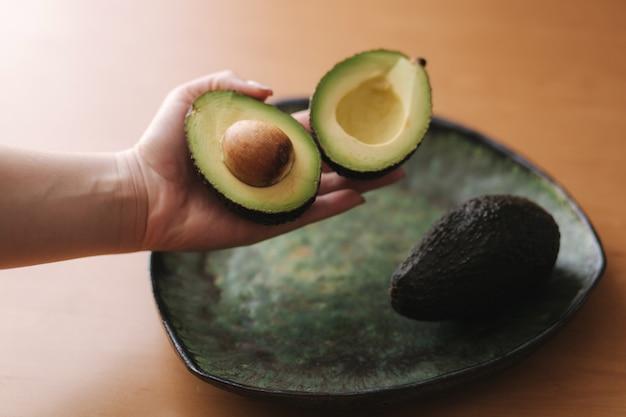 Свежий нарезанный авокадо в руке женщины на зеленой тарелке. концепция вегетарианской пищи.