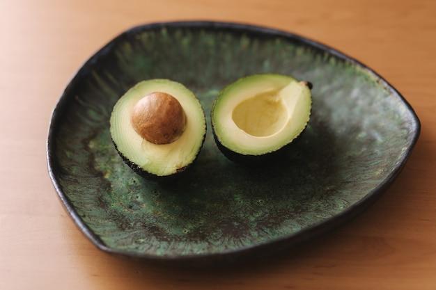 Свежий нарезанный авокадо на зеленой тарелке. концепция вегетарианской пищи
