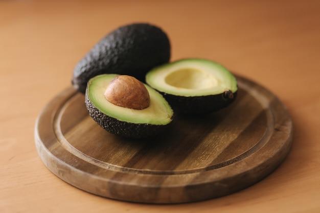Свежий нарезанный авокадо на деревянной доске. концепция вегетарианской пищи.