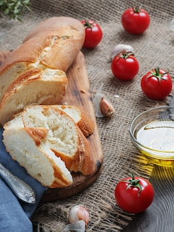Fresh sliced baguette, tomatoes and olive oil, ingredients for making a sandwich