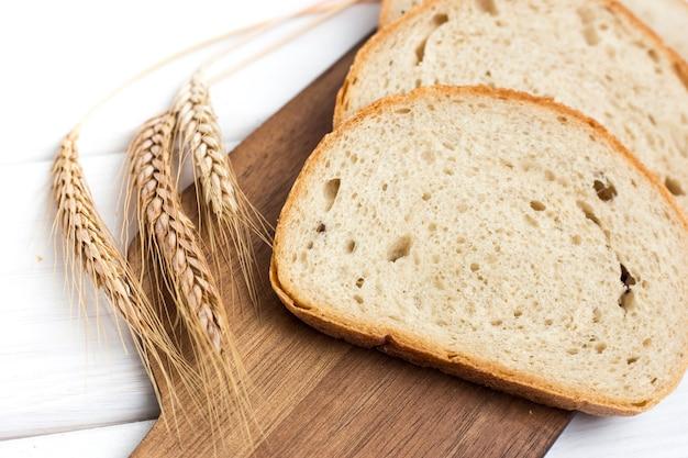 白い木製のテーブル、上面図の木製まな板に新鮮なスライスされたパンと小麦