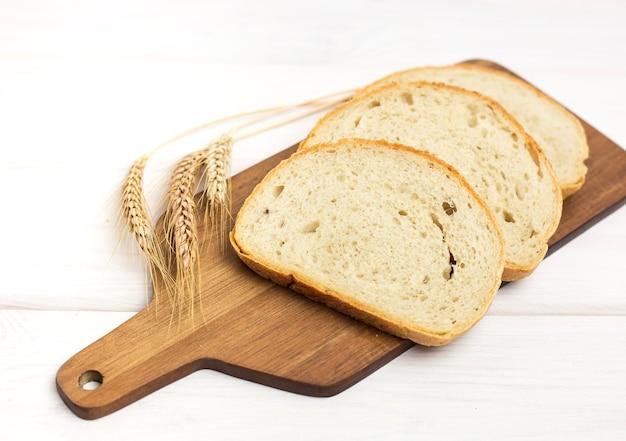 白い木製のテーブルの上の木製まな板に新鮮なスライスされたパンと小麦