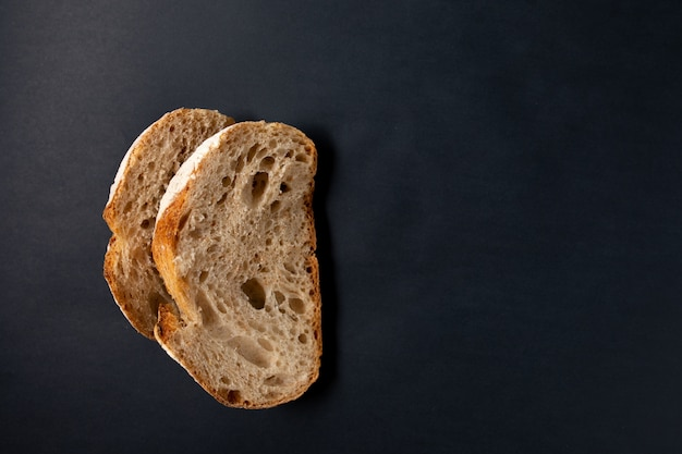 Fresh sliced bread on a black surface. view from above