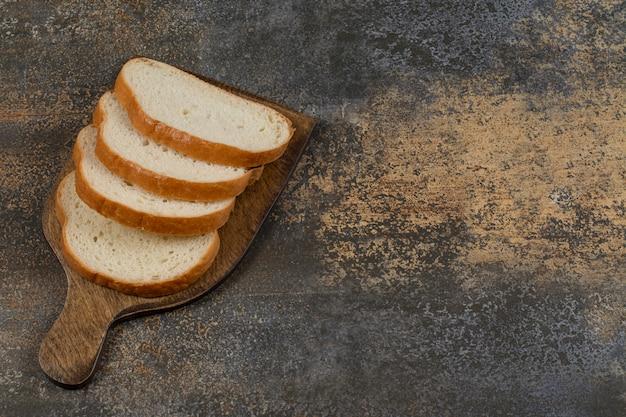 나무 보드에 신선한 슬라이스 빵입니다.