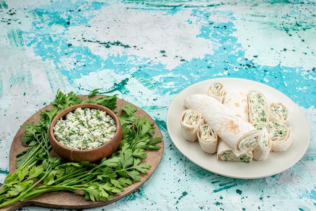 新鮮なスライスしたキャベツのサラダ、茶色のボウルの中に緑があり、明るい青色の机の上に野菜のロールがあります