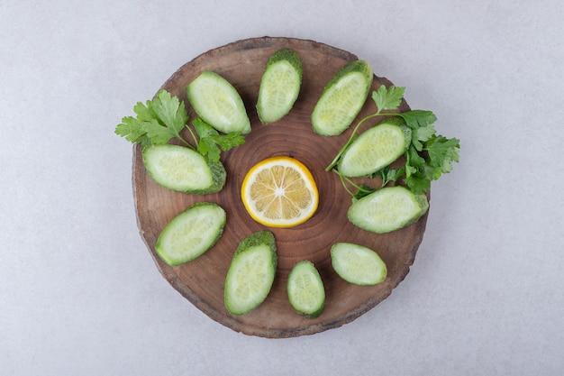 Свежий, нарезанный огурец, лимон и петрушка на доске на мраморном столе.