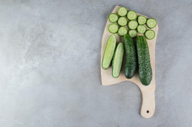 Cetrioli affettati freschi con coltello su una tavola di legno. foto di alta qualità