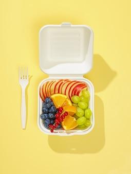노란색 배경에 격리된 흰색 테이크아웃 상자에 신선한 얇게 썬 과일과 열매
