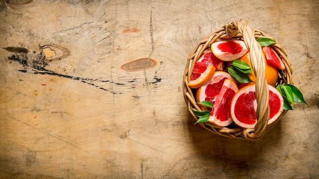 木製のテーブルの上のバスケットに新鮮なスライスしたグレープフルーツ。上面図