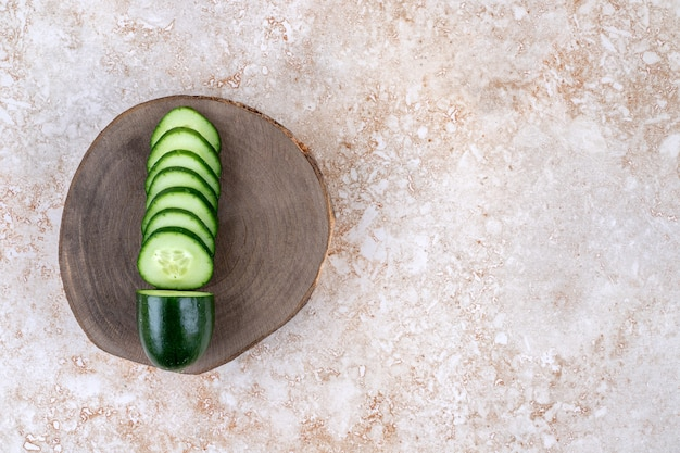 Fresh sliced healthy sliced cucumbers on wood board.
