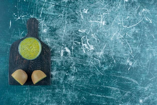 Свежий нарезанный киви рядом с соком на разделочной доске на синем фоне.