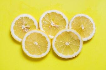 黄色の明るい背景に新鮮なスライスレモンリング