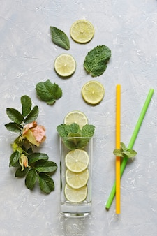Fresh sliced lime with green mint leaves, and glass on grey table background. top view