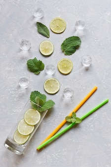 Fresh sliced lime with green mint leaves, ice and glass on grey table background. top view