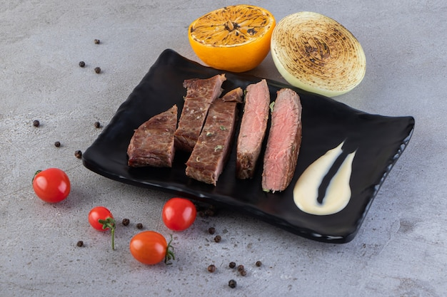 신선한 야채와 함께 신선한 슬라이스 고기를 돌 테이블에 배치합니다.