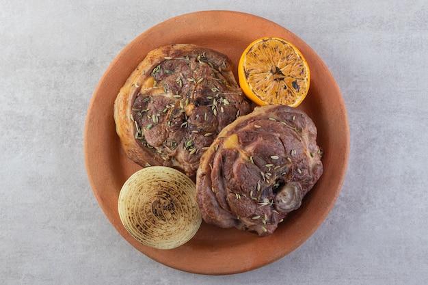 石のテーブルに置かれた新鮮な野菜と新鮮なスライス肉。