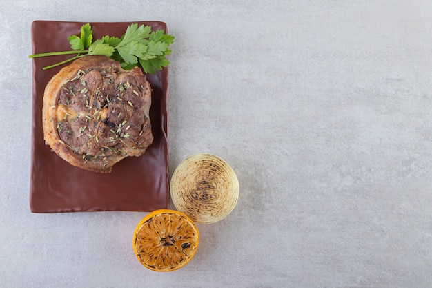 Fresh sliced meat with fresh vegetables placed on a stone background.